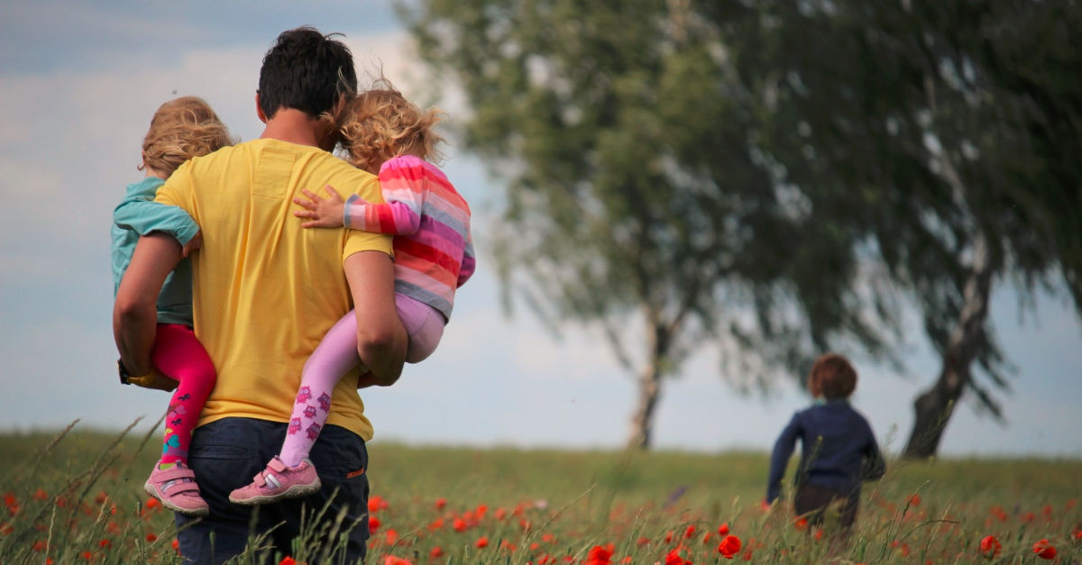 father and children in a field